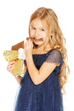 Beautiful girl with chocolate. Beautiful blonde girl in a blue dress with curls eating a chocolate Royalty Free Stock Images