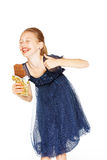 Beautiful girl with chocolate. Beautiful blonde girl in a blue dress with curls eating a chocolate Royalty Free Stock Photography