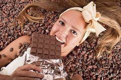 Beautiful girl with chocolate on cocoa beans Stock Photo