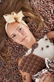 Beautiful girl with chocolate on cocoa beans Royalty Free Stock Image