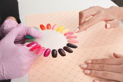 Beautiful girl choose color of nail polishes stock photography