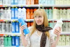 Beautiful girl chooses abstergents in shop Royalty Free Stock Photos