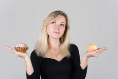 Beautiful girl chooses between an apple and a cake Royalty Free Stock Images