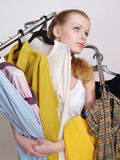 The beautiful girl chooses clothes in shop Royalty Free Stock Image