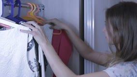 Beautiful girl chooses dress in her wardrobe. stock video