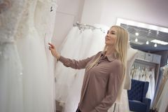 Beautiful girl chooses her wedding dress. Young woman entrepreneur. Portrait in Bridal salon Royalty Free Stock Images