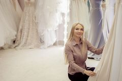 Beautiful girl chooses her wedding dress. Young woman entrepreneur. Portrait in Bridal salon. Beautiful girl chooses her wedding dress. A young woman Royalty Free Stock Photos