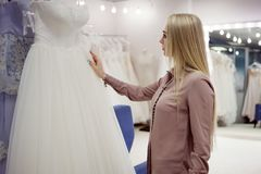 Beautiful girl chooses her wedding dress. Young woman entrepreneur. Portrait in Bridal salon Royalty Free Stock Photos
