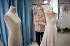Beautiful girl chooses her wedding dress. Young woman entrepreneur. Portrait in Bridal salon Stock Photos
