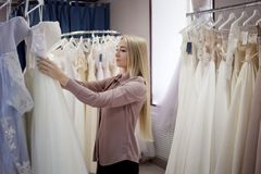Beautiful girl chooses her wedding dress. Young woman entrepreneur. Portrait in Bridal salon Royalty Free Stock Photography