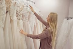 Beautiful girl chooses her wedding dress. Young woman entrepreneur. Portrait in Bridal salon Royalty Free Stock Photo