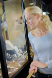 Beautiful girl chooses jewellery in shop window. Beautiful girl chooses jewellery in the shop window Royalty Free Stock Photos