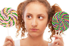 Beautiful girl chooses from two sugar candies Stock Images
