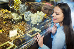 Beautiful girl choosing delicious ganaches and chocolates Royalty Free Stock Photo