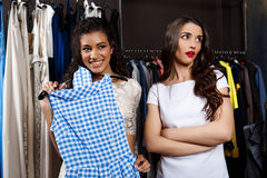 Beautiful girl choosing dress in mall. Another one displeased. Royalty Free Stock Images