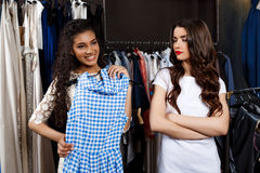 Beautiful girl choosing dress in mall. Another one displeased. Stock Photo