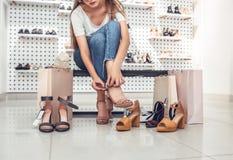 Beautiful girl is choosing high-heeled shoes. stock photos