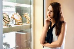 Beautiful girl choosing jewelry in shop. Young woman with long dark hair chooses jewellery in the shop window Royalty Free Stock Photography