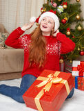 Beautiful girl in christmas decoration. Home interior with decorated fir tree and gifts. New year eve and winter holiday concept. Royalty Free Stock Images