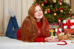 Beautiful girl in christmas decoration. Home interior with decorated fir tree and gifts. New year eve and winter holiday concept. Stock Image