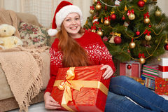 Beautiful girl in christmas decoration. Home interior with decorated fir tree and gifts. New year eve and winter holiday concept. Stock Photos