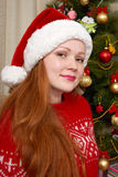 Beautiful girl in christmas decoration. Home interior with decorated fir tree and gifts. New year eve and winter holiday concept. Stock Photography