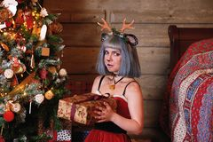 Beautiful girl in a Christmas deer costume near to Christmas tree and new year presents Stock Images