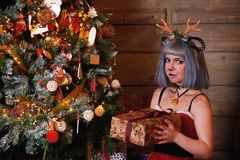 Beautiful girl in a Christmas deer costume near to Christmas tree and new year presents Stock Photography