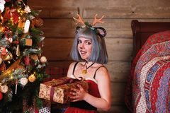 Beautiful girl in a Christmas deer costume near to Christmas tree and new year presents Stock Image