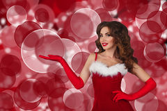 Beautiful girl in christmas dress with extended hand. copy space. Stock Image