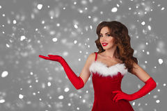 Beautiful girl in christmas dress with extended hand  - isolated over a grey background  with snow. copy space. Stock Photo