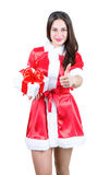 Beautiful girl in Christmas dress holding present with a gesture stock photo