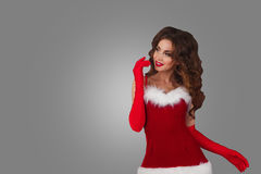 Beautiful girl in christmas dress  over a grey background. woman looking to the left of the frame towards blank copy space Royalty Free Stock Image