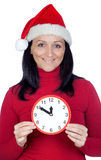 Beautiful girl with Christmas hat and a clock Royalty Free Stock Image
