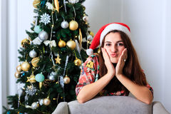 Beautiful girl in Christmas hat next to Christmas tree Royalty Free Stock Images