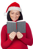 Beautiful girl with Christmas hat reading a book Royalty Free Stock Images