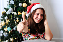 Beautiful girl in Christmas hat showing thumbs up sign OK Stock Images
