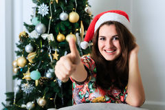 Beautiful girl in Christmas hat showing thumbs up sign OK Stock Photo