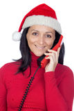 Beautiful girl with Christmas hat to phone Royalty Free Stock Images