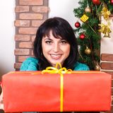Beautiful girl in a christmas interior gives a red gift box, loo Stock Image