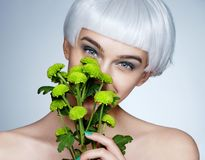 Beautiful girl with chrysanthemum flowers on blue background. Youth and skin care concept Royalty Free Stock Photo