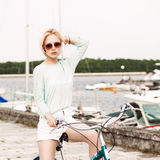 Beautiful girl with city bike at sea pier Stock Image