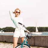 Beautiful girl with city bike at sea pier Stock Photo