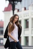 Beautiful girl in the city. Beautiful girl walks on the square in the city with a black coat Stock Photo
