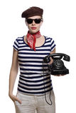 Beautiful girl in classic 60s french look. Beautiful girl with red bandana, beret and striped shirt in a classic 60s french look is holding an old rotary phone stock photo