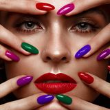 Beautiful girl with a classic make-up and multi-colored nails. Manicure design. Beauty face. royalty free stock images
