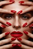 Beautiful girl with a classic make-up and red nails. Manicure design. Beauty face. stock photos