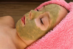Beautiful girl with clay mask facial.  Royalty Free Stock Photography