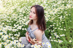 Beautiful girl with clock on hand in dress sits in chamomile Royalty Free Stock Photos