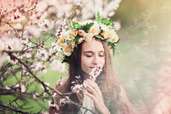 Beautiful girl with closed eyes dressed in wreath of flowers royalty free stock image